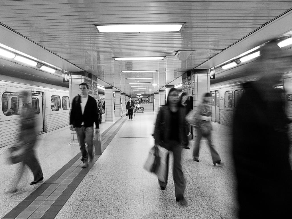 black and white image of people moving on subway platform