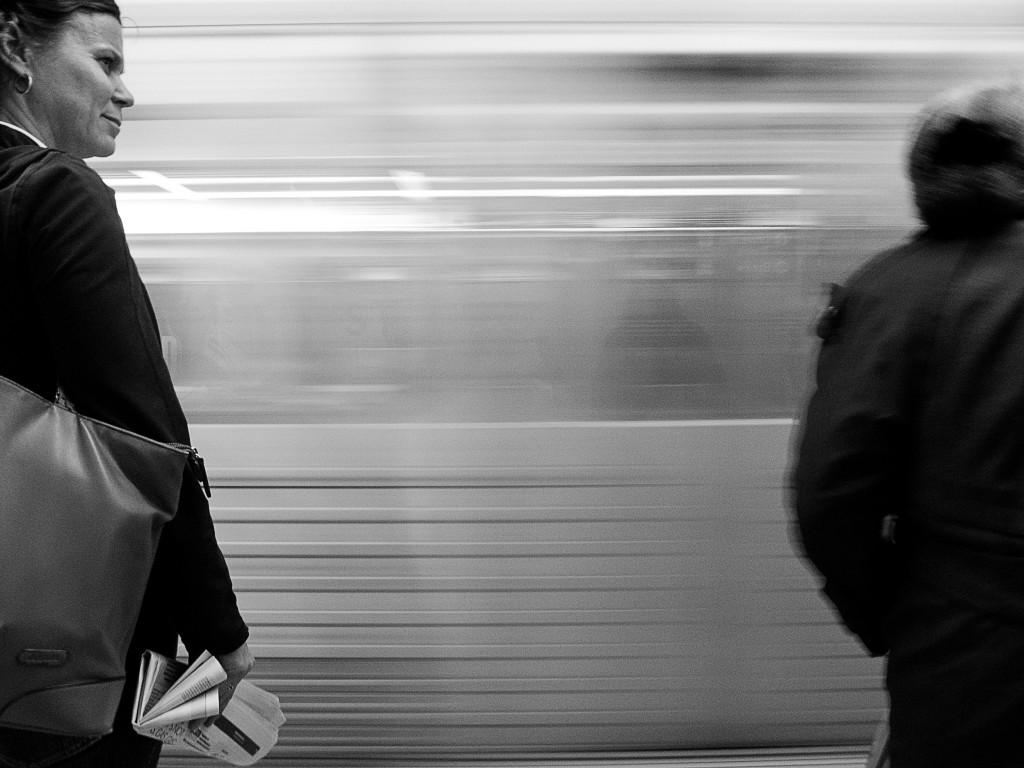 woman looks down subway platform as subway train speeds behind her
